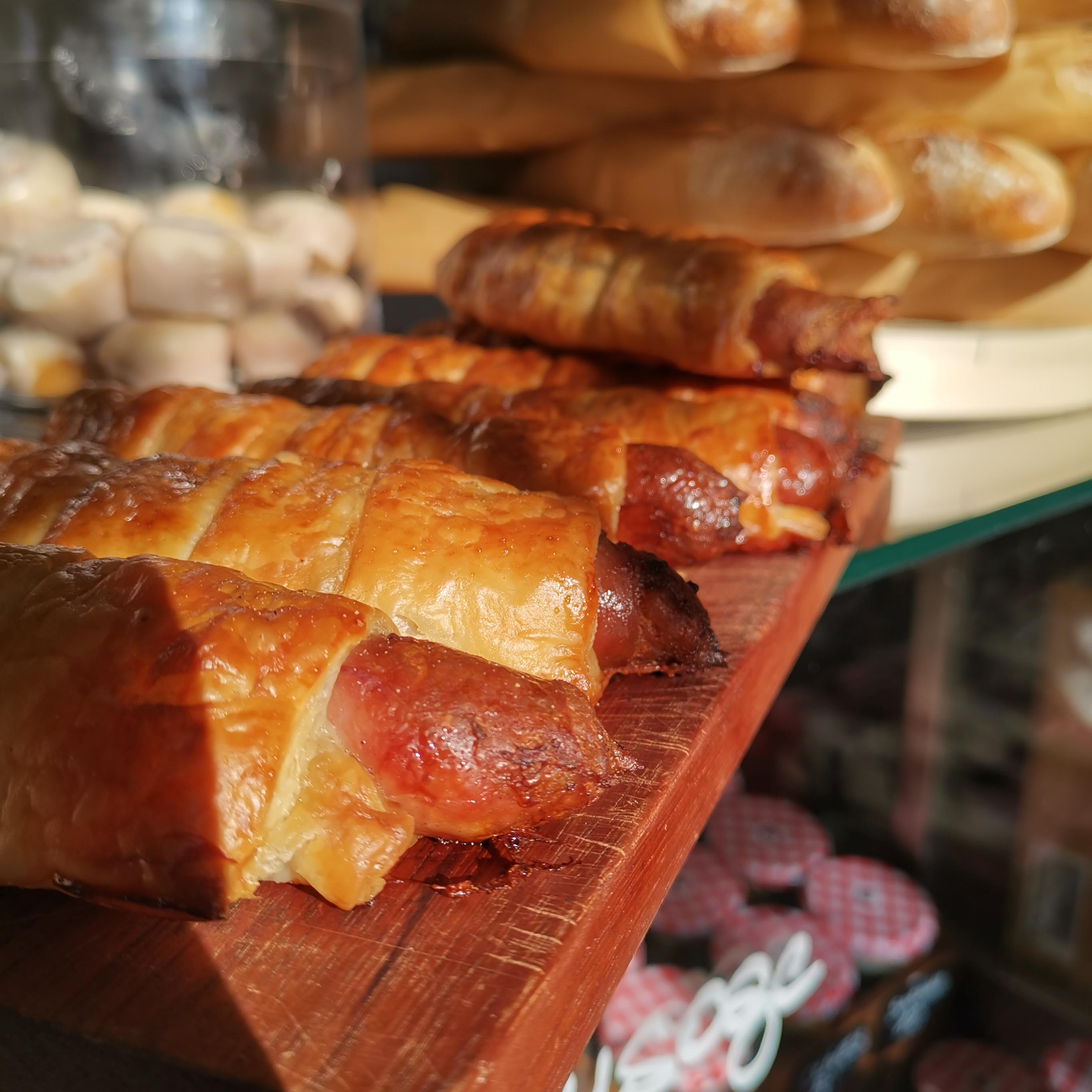 Pastry wrapped sausages on wooden board