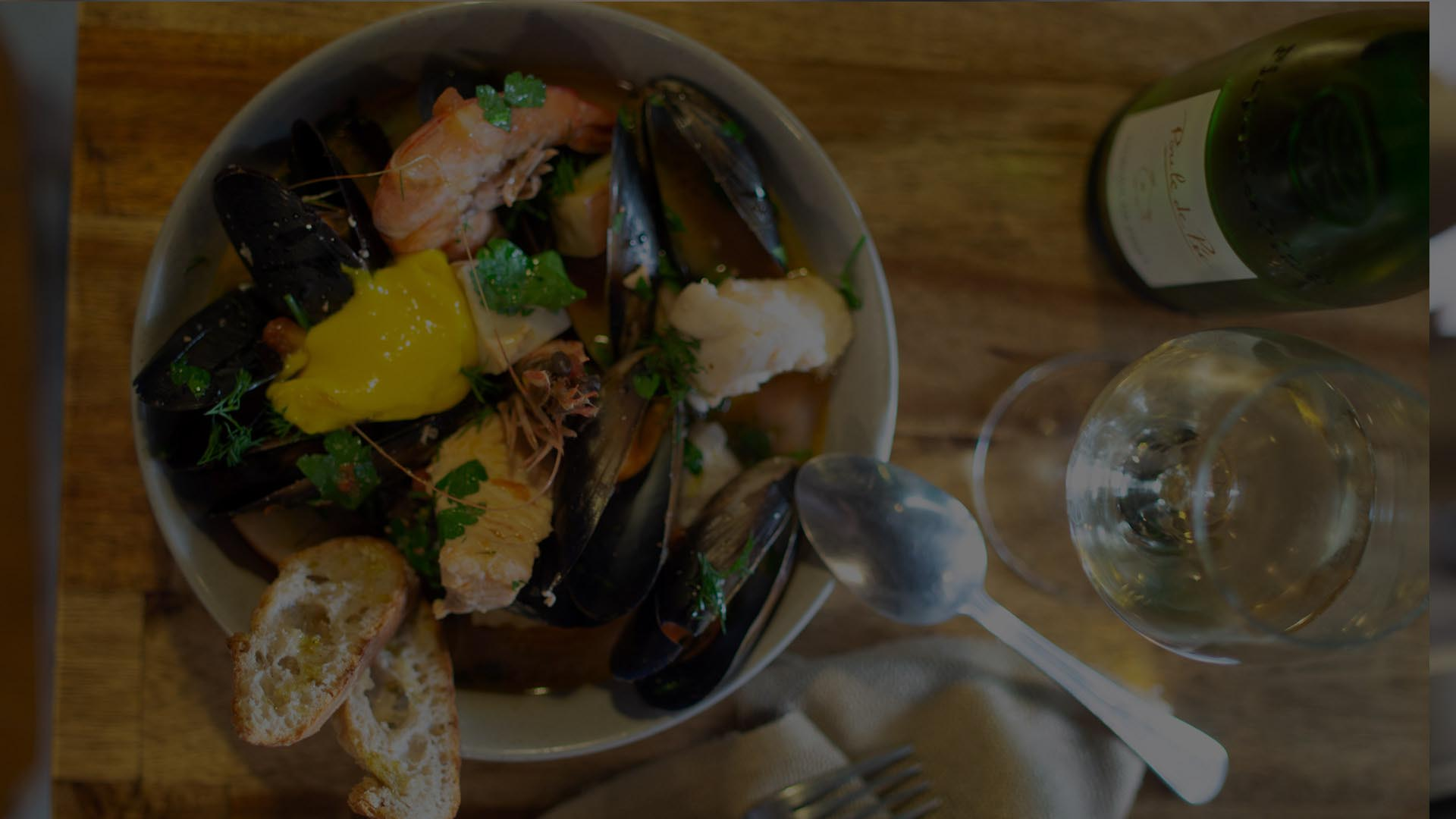 seafood bouillabaisse, crusty bread and wine